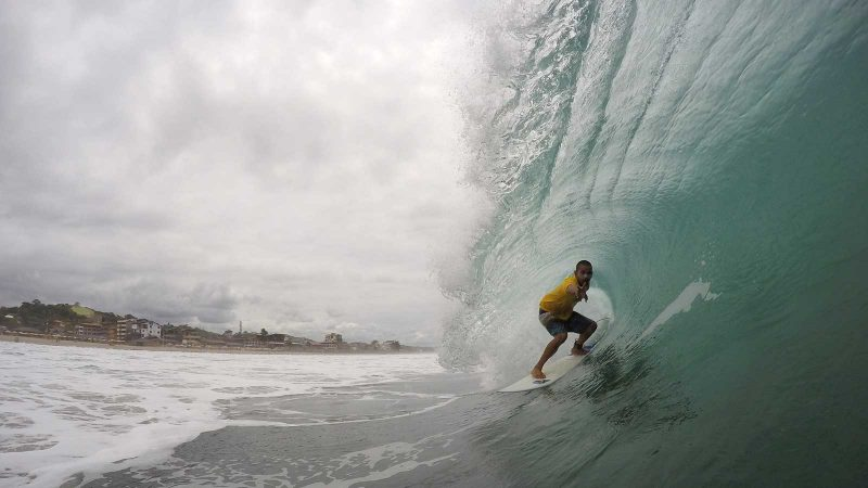 A surfer rides a tube, with Montanita in the background